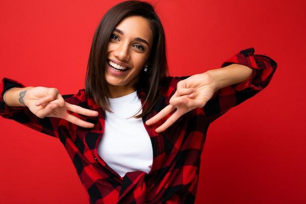 Nahaufnahme der jungen glücklichen positiven lächelnden kühlen schönen brunetfrau mit aufrichtigen gefühlen, die weißes t-shirt und stilvolles rotes karohemd einzeln über rotem hintergrund mit kopienraum tragen.