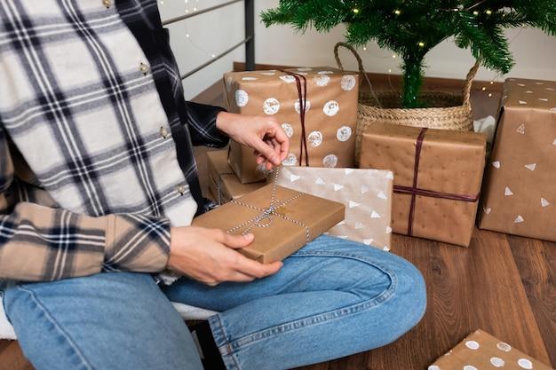 Nahaufnahme der jungen kaukasischen frau, die eingewickeltes weihnachtsgeschenk öffnet. urlaubskonzept.