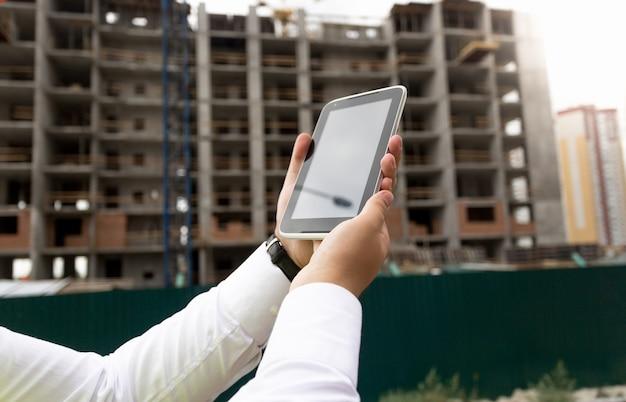 Nahaufnahme der jungen männlichen hand, die digitales tablet mit baustelle im hintergrund hält