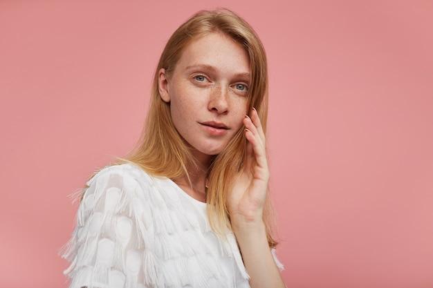 Nahaufnahme der jungen nachdenklichen attraktiven rothaarigen frau mit natürlichem make-up, das weiches gesicht mit erhabener hand berührt und kamera mit ruhigem gesicht betrachtet, lokalisiert über rosa hintergrund