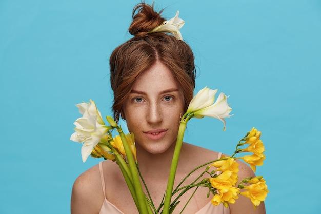 Nahaufnahme der jungen positiven attraktiven grünäugigen frau, die ihr foxy haar im knoten trägt, während über blauem hintergrund mit bündel frühlingsblumen steht