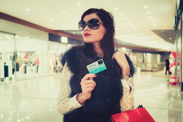 Nahaufnahme der jungen schönen frau mit kreditkarte und tasche in den händen am einkaufszentrumhintergrund. schickes mädchen kauft mit zahlungskarte ein. die reiche dame wird etwas auf dem luxusplatz kaufen.