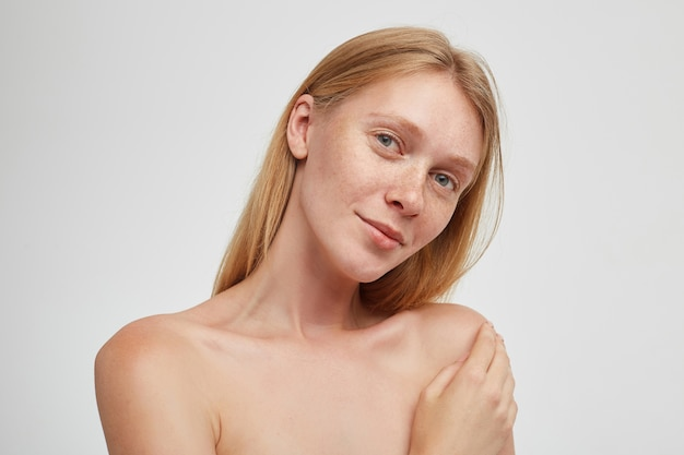 Nahaufnahme der jungen schönen rothaarigen frau mit natürlichem make-up, das positiv mit weichem lächeln schaut und erhabene handfläche auf ihrer schulter hält, lokalisiert über weißer wand