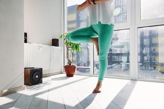Nahaufnahme der jungen schönen sportlichen frau, die yoga praktiziert und baumhaltung zu hause gegen große fenster durchführt