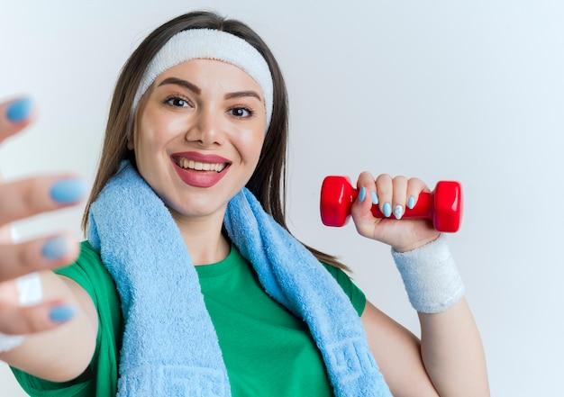 Nahaufnahme der jungen sportlichen frau, die stirnband und armbänder mit handtuch um hals hält hantel trägt