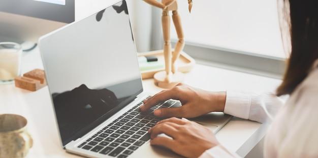 Nahaufnahme der jungen weiblichen hand, die auf laptop schreibt