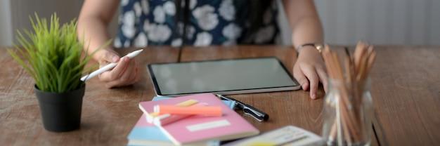 Nahaufnahme der jungen weiblichen universität, die sich auf tablett mit leerem bildschirm konzentriert, um informationen zu finden