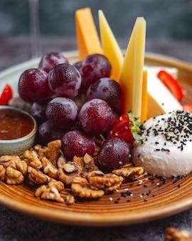 Nahaufnahme der käseplatte mit walnüssen, trauben und erdbeeren
