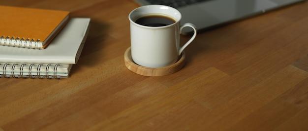 Nahaufnahme der kaffeetasse auf hölzernem arbeitstisch mit notizbüchern und laptop