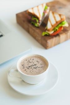 Nahaufnahme der kaffeetasse mit sandwichen auf hölzernem hackendem brett