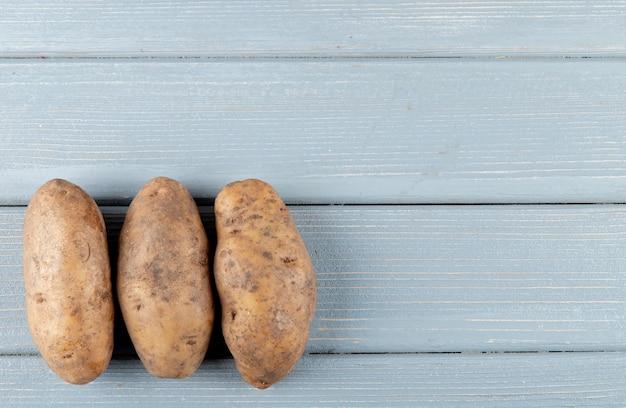 Nahaufnahme der kartoffeln auf der linken seite und des hölzernen hintergrunds mit kopienraum 2