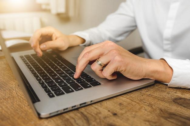 Nahaufnahme der kaukasischen mannhand, die auf laptop auf büroholzschreibtisch tippt. mail schreiben. online einkaufen. online-banking. tippen am computer