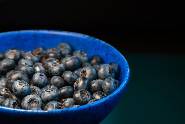 Nahaufnahme der keramikschale voll von blaubeeren auf blauem hintergrund.