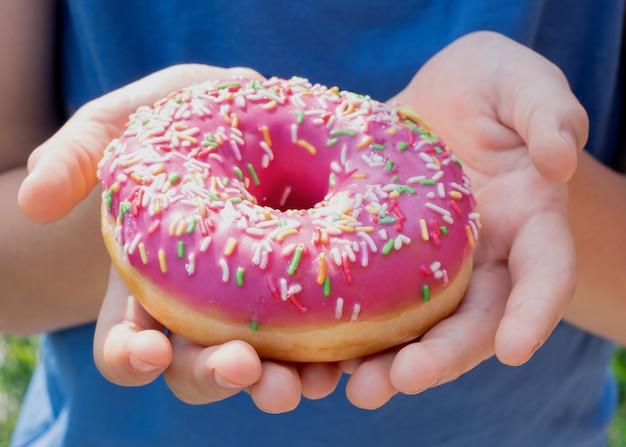 Nahaufnahme der kinderhände, die einen donut mit rosa zuckerguss halten und streuen
