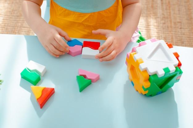 Nahaufnahme der kinderhände sammeln puzzlesortierer. würfel mit eingefügten geometrischen formen und farbigen kunststoffblöcken.