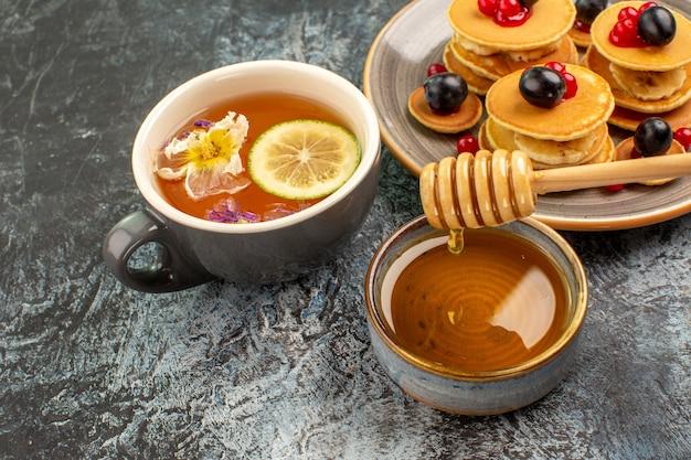Nahaufnahme der klassischen amerikanischen pfannkuchen mit honig und einer tasse tee