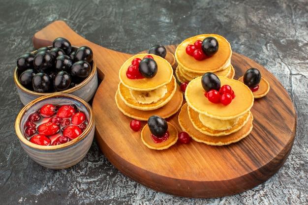 Nahaufnahme der klassischen buttermilchpfannkuchen, die mit früchten auf grau serviert werden