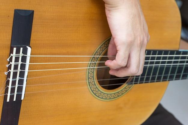 Nahaufnahme der klassischen gitarrensaiten mit den fingern