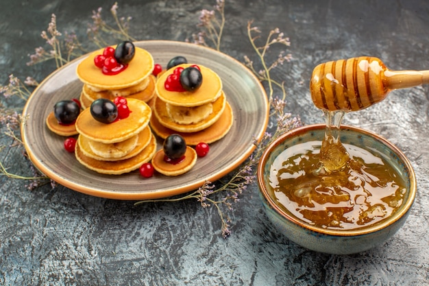 Nahaufnahme der klassischen hausgemachten pfannkuchen und des honigs auf grau