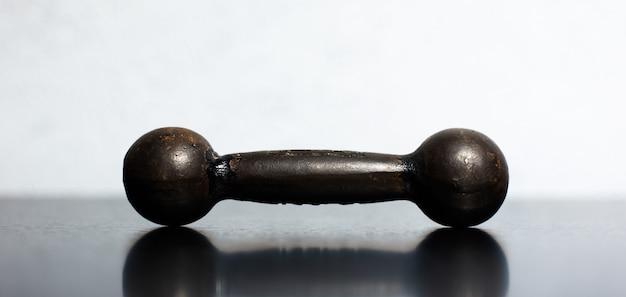 Nahaufnahme der kleinen hantel auf schwarzem tisch