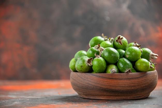 Nahaufnahme der kleinen vitaminbombe grün feijoas in einem braunen holztopf