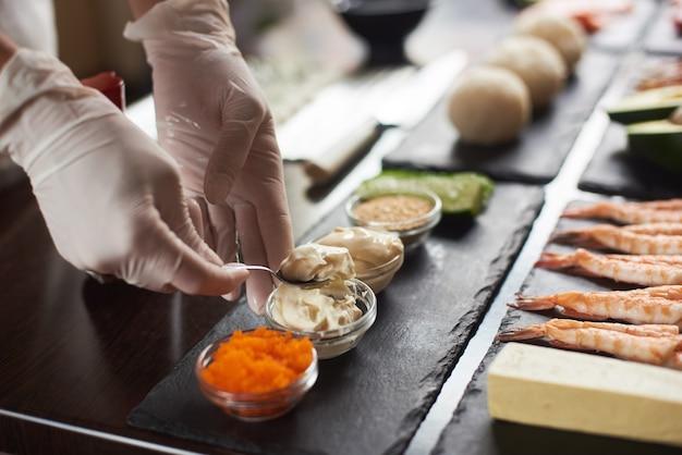 Nahaufnahme der kochhände, die japanisches essen vorbereiten. japanischer koch, der sushi-rollen im restaurant macht.