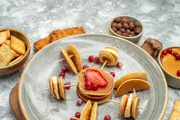 Nahaufnahme der köstlichen pfannkuchenplätzchen und -kuchen zum frühstück auf schneidebrett auf blau
