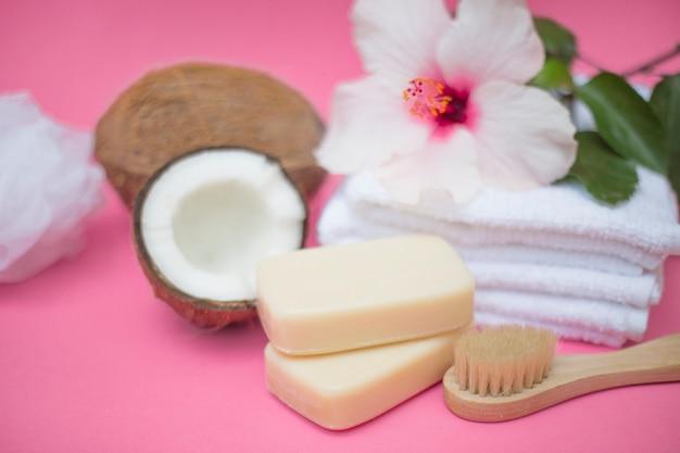 Nahaufnahme der kokosnuss; seife; bürste; blume und handtücher auf rosa hintergrund