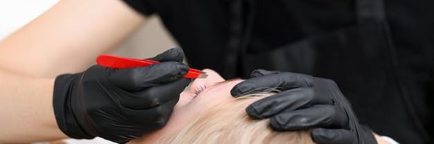 Nahaufnahme der kosmetikerin, die handschuhe trägt und augenbrauen mit einer pinzette zupft. salonarbeiterin bereitet frauenbrauen für dauerhaftes make-up vor. mua und schönheitsbehandlungskonzept