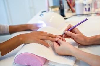 Nahaufnahme der Kosmetikerin die Nägel einer Frau mit einer Bürste in einem Nagelsalon malend