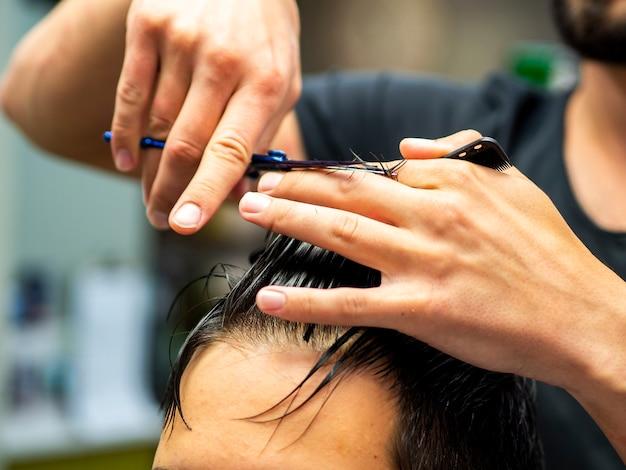 Nahaufnahme der kosmetikerin haare schneiden
