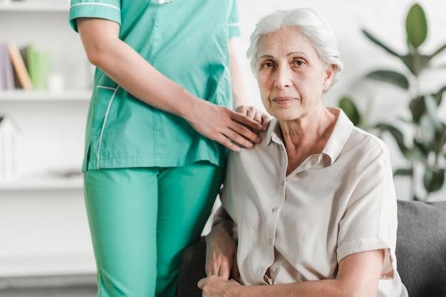 Nahaufnahme der krankenschwester stehend mit dem älteren weiblichen patienten, der auf sofa sitzt
