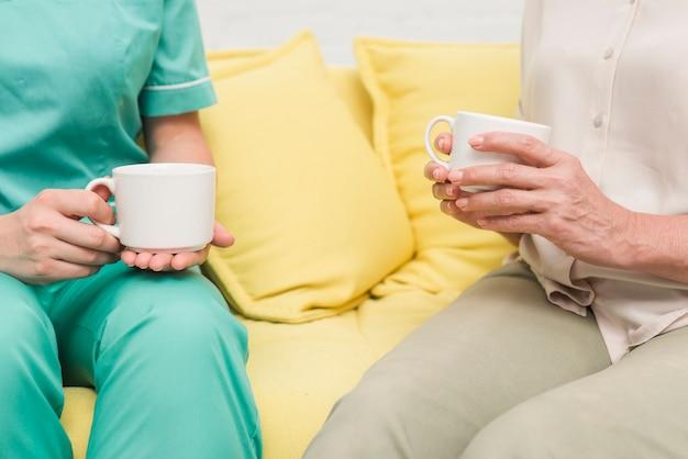 Nahaufnahme der krankenschwester und des patienten, die auf dem sofa hält kaffeetassen sitzen
