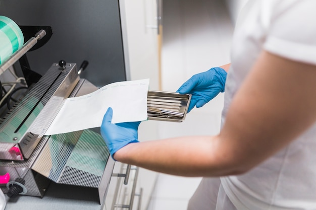 Nahaufnahme der krankenschwesterhand dental instrument mit plastik verpackend