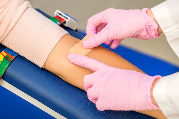 Nahaufnahme der krankenschwesterhand, die nach der blutentnahme im krankenhaus heftpflaster auf den arm des patienten aufträgt