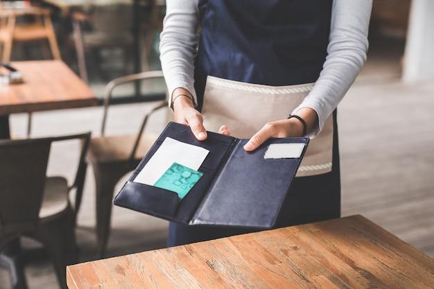 Nahaufnahme der kundenhand, die seine rechnungen mit kreditkarte bezahlt