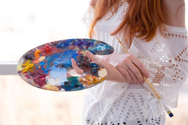 Nahaufnahme der kunstpalette mit ölfarben und pinsel, gehalten von einer jungen frau mit roten haaren in weißer bluse