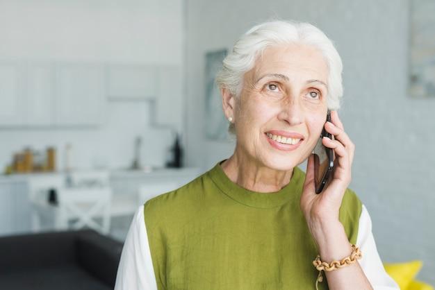 Nahaufnahme der lächelnden älteren frau, die auf mobiltelefon spricht