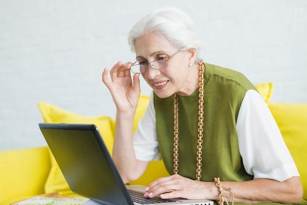 Nahaufnahme der lächelnden älteren frau, die laptop betrachtet