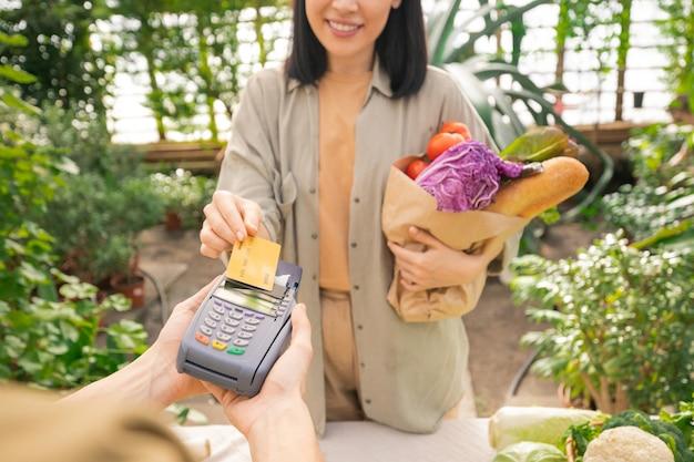 Nahaufnahme der lächelnden dame, die papiertüte voll des gemüses hält und für bio-lebensmittel mit kreditkarte im lebensmittelgeschäft zahlt