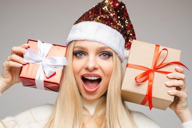 Nahaufnahme der lächelnden hübschen dame, die weihnachtsmützen trägt und mit geschenken aufwirft