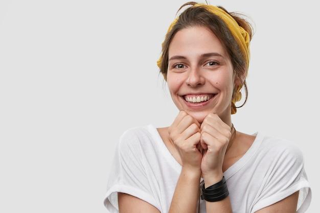 Nahaufnahme der lächelnden hübschen frau mit freudigem gesichtsausdruck, hält hände unter kinn, schaut glücklich direkt