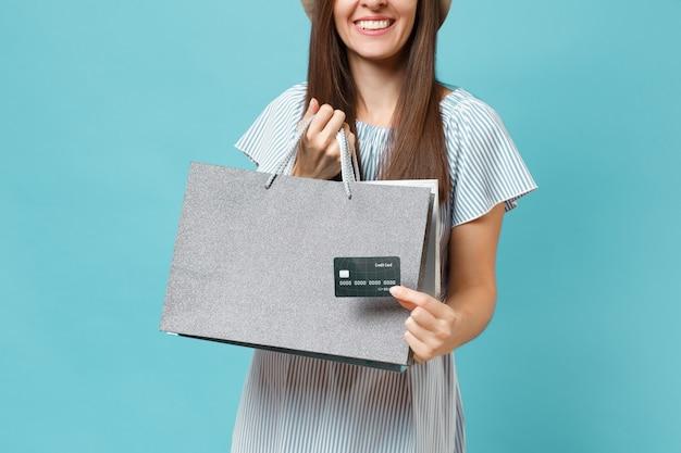 Nahaufnahme der lächelnden hübschen kaukasischen frau im sommerkleid, die pakete mit einkäufen nach dem einkauf hält, bankkreditkarte einzeln auf blauem pastellhintergrund. kopieren sie platz für werbung.