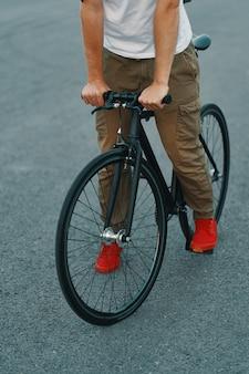 Nahaufnahme der lässigen mannbeine, die klassisches fahrrad auf stadtstraße fahren