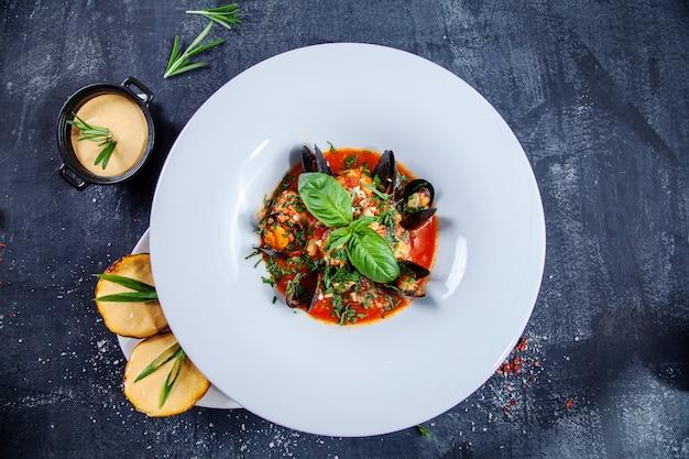 Nahaufnahme der leckeren meeresfrüchtesuppe in der weißen restaurantschüssel. bouillabaisse mit muscheln, lachs und basilikum mit einem snack aus kartoffeln mit käsesauce. dunkler hintergrund. lebensmittelfoto für menü oder rezept