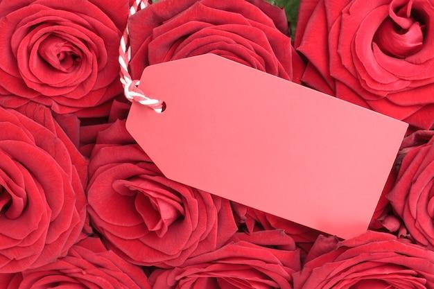 Nahaufnahme der leeren marke mit roten rosen. valentinstag-konzept
