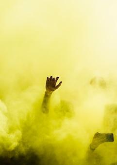 Nahaufnahme der leute tanzen und in der gelben explosion der holi farbe