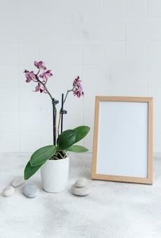 Nahaufnahme der lila phalaenopsis-orchidee im topf und verspotten sie plakatrahmen auf dem tisch