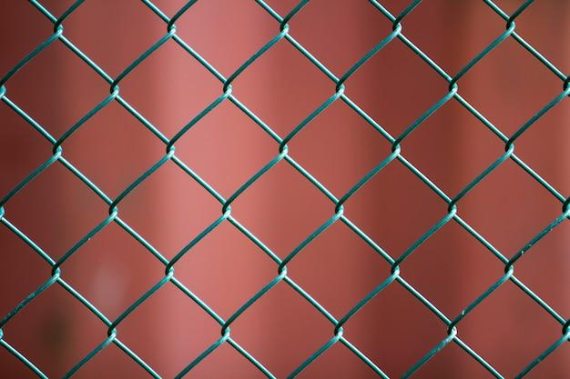 Nahaufnahme der lokalisierten gemalten einfachen geometrischen dunkelroten szene des schwarzen eisenmetalldrahtkettengliedzauns eon. zaun-, schutz- und gehegekonzept.