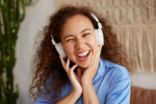 Nahaufnahme der lustigen lockigen jungen mulattendame, die lieblingsmusik in kopfhörern hört, den sonntagmorgen genießt, zwinkert und breit lächelt.